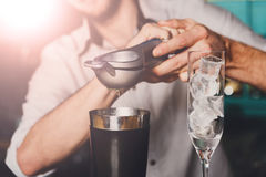 Barmans hands making cocktail with lime Royalty Free Stock Image