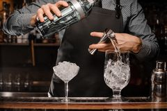 Barmans hands pouring alcoholic drink into a glass using a jigger to prepare a cocktail Stock Image