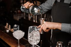 Barmans hands pouring alcoholic drink into a jigger to prepare a fresh cocktail Royalty Free Stock Photos