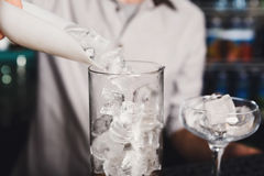 Barmans hands pouring ice for cocktail Royalty Free Stock Photo