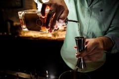 Barmans räcker att hälla en sirap för framställning av en coctail arkivbilder