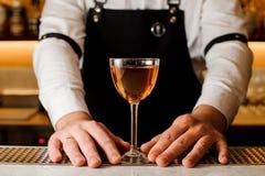 Barmans räcker att rymma ett exponeringsglas med alkoholdrycken royaltyfria bilder