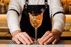 Barmans räcker att rymma ett exponeringsglas med den plaskande alkoholdrycken royaltyfri fotografi