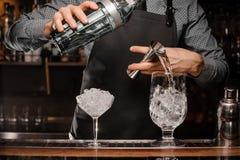 Barmans räcker den hällande alkoholdrycken in i ett exponeringsglas genom att använda en grej för att förbereda en coctail fotografering för bildbyråer