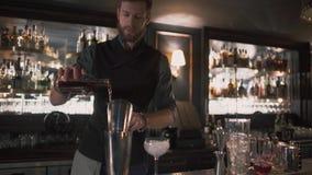 Barmanu dolewania alkohol w zlewce w szkle z lodem wtedy, demonstruje jego umiejętności Barman robi koktajlowi w nowożytnym zbiory