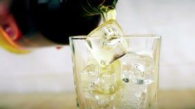 Barmanu dolewania whisky w szkle z kostkami lodu na drewno stołu tle, ostrość na kostkach lodu, whisky relaksuje czas, złoto ciep zbiory