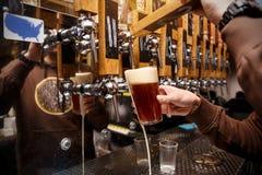 Barmanu dolewanie od kranowego świeżego piwa w szkło w pubie obrazy stock