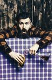 Barmanu overdrink, pijący Mężczyzna w w kratkę koszula na drewnianym tle, błękitny tablecloth zdjęcia stock
