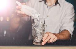 Barmanu ` s wręcza dolewanie lód dla koktajlu obraz stock