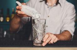 Barmanu ` s wręcza dolewanie lód dla koktajlu obraz royalty free