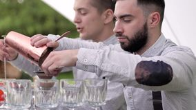 Barmen across strainer pours drinks, bartender do alcoholic tipple, hands bartender pours into glass. Barkeeper makes beverage for client, tapster standing stock video footage