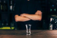 Barmen hand with bottle pouring beverage into glass. Bartender pouring strong alcoholic drink into small glass on bar stock photo