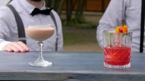 Barmen serves alcohol, close-up, barkeeper decorated colored drinks on bar counter, in hands bartenders chilled drinks stock footage
