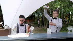 Barmen show outdoors, two barkeeper mix in shaker cocktail, bar workers prepare drinks in mixing glass with filter. Serves alcohol colored drink on bar counter stock video