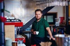 Barmixer barista mit Kaffee in der Hand hinter dem Tresen Stockbilder