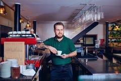 Barmixer barista mit Kaffee in der Hand hinter dem Tresen Lizenzfreies Stockbild