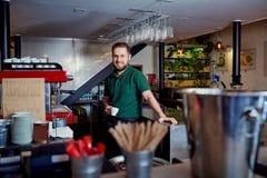 Barmixer barista mit Kaffee in der Hand hinter dem Tresen am brea Lizenzfreie Stockfotos