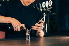 Barmixer, der Alkohol coctail im Restaurant macht Sachverständiger Kellner fügt Bestandteilcocktail am Nachtklub hinzu stockbilder
