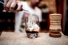 Barmixer, der alkoholischen Alkohol im kleinen Glas auf dem Zähler gießt Lizenzfreie Stockfotos