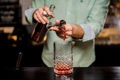 Barmixer, der alkoholisches Cocktail, Metalljigger und Barumwelt macht stockfoto