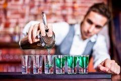 Barmixer, der blaue Curaçao-Alkoholikercocktails gießt Stockbilder