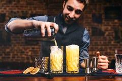 Barmixer, der Cocktails vorbereitet und frischen Alkohol in den Gläsern gießt Cocktails dienten in der Bar, im Restaurant oder in Stockbild
