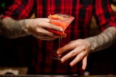 Barmixer, der ein Cocktail kosmopolitisch in der Bar dient lizenzfreie stockfotografie
