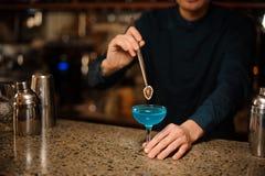 Barmixer, der ein Glas des frischen Sommercocktails mit blauem Alkohol unter Verwendung einer Scheibe der Orange decoating ist Lizenzfreies Stockfoto