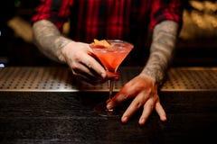 Barmixer, der ein köstliches Cocktail kosmopolitisch in der Bar dient lizenzfreies stockfoto
