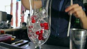 Barmixer, der ein leeres Glas mit Eis und Moosbeere gießt stock footage