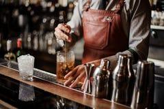 Barmixer, der heraus mischendes Eis des Cocktailglases mit einem Löffel abkühlt lizenzfreie stockfotografie