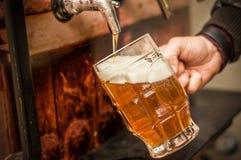 Barmixer, der mit einem blonden Handwerksbier in ein Pint-Glas auffüllt stockfoto