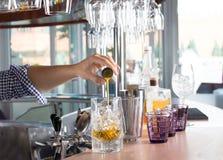 Barmixer, der Stahljigger hält und orange Alkohol in Th gießt Stockfotos