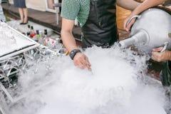 Barmixer dienen das Cocktail in einer großen Schüssel mit flüssigem Stickstoff rudern Sie Linie von verschiedenen alkoholischen C lizenzfreies stockfoto