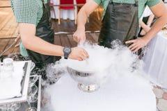 Barmixer dienen das Cocktail in einer großen Schüssel mit flüssigem Stickstoff rudern Sie Linie von verschiedenen alkoholischen C stockfoto