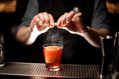 Barmixer drückt eine orange Rinde im Alkoholcocktail zusammen lizenzfreie stockfotos