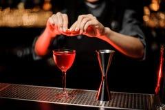 Barmixer drückt orange Rinde im Alkoholcocktail zusammen stockbild