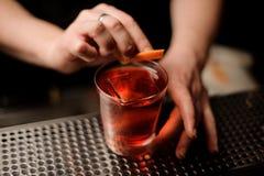 Barmixer fügt orange Rinde im Alkoholcocktail hinzu stockfotografie