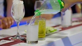Barmixer gießt funkelndes Wasser in einem Glas mit Eis stock video