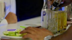 Barmixer gießt funkelndes Wasser in einem Glas mit Eis stock video footage