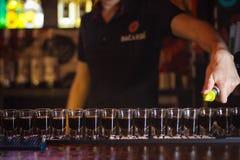 Barmixer gießt viele alkoholischen Schüsse Stockfotografie