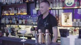 Barmixer gießt weiße sahnige Flüssigkeit vom Schüttel-Apparat innerhalb des überraschenden weißen Cocktailglases Nachtleben stock video