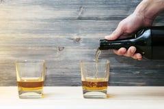 Barmixer gießt zwei Gläser Alkohol Stockfotografie