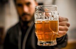 Barmixer holdinga füllte köstliches blondes Handwerksbier in ein Pint-Glas stockfoto