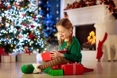 Barnöppning som är närvarande på julgranen hemma Unge i älvadräkt med Xmas-gåvor och leksaker Liten flicka med den gåvaasken och  royaltyfria foton