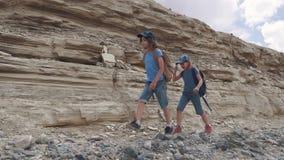 Barn är handelsresande på en vandring En liten turist med ryggsäckar promenerar den bergiga terrängen stock video