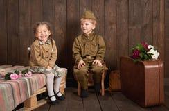 Barn är iklädda retro militära likformig som överför en soldat till armén, mörk wood bakgrund, retro stil Arkivbild