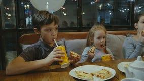 Barn äter pizza på kafét och äter potatisar Royaltyfri Foto