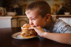 Barn äter söta pannkakor för frukost royaltyfria foton