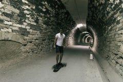 Barn 20-25 år gamal man i tunnel med skateboarden Omgivande lig fotografering för bildbyråer